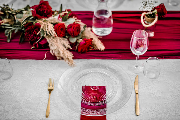 Feestlocatie Diner tafel in rood thema met goud bestek