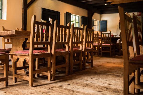 Hofstede sfeerfoto van de houten tafels met robuuste houten stoelen